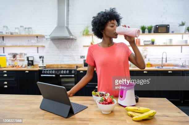 african american woman at home drinking a smoothie - juice drink stock pictures, royalty-free photos & images