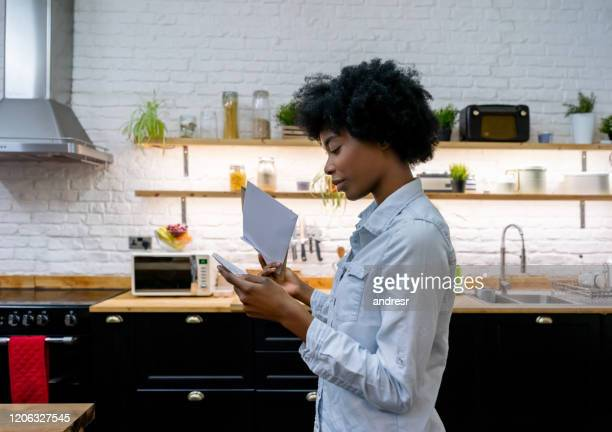 african american woman at home reading the mail - monogram stock pictures, royalty-free photos & images