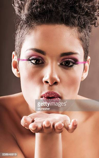 African American woman blowing a kiss.