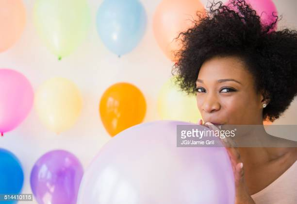 African American woman blowing up balloon for party