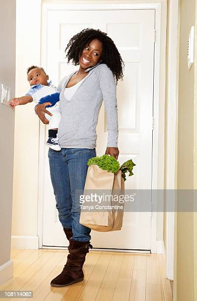 African American woman carrying bag of groceries. baby son and talking on phone