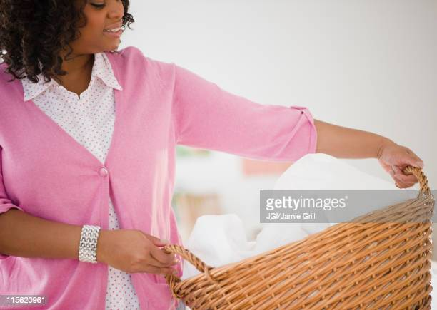African American woman carrying laundry basket