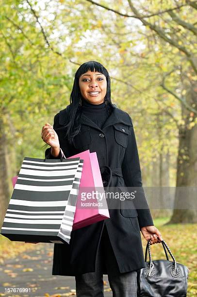 African American Woman Carrying Shopping Bags During Autumn/ Winter Season
