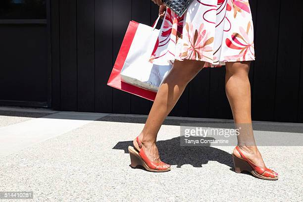 African American woman carrying shopping bags on city street