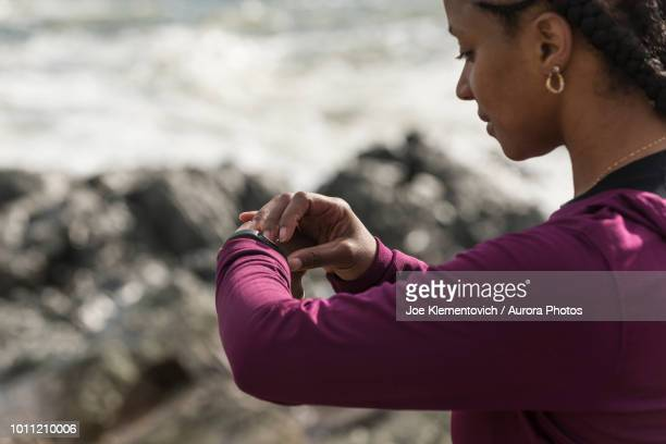 African American woman checking fitness tracker while running, Kittery, Maine, USA