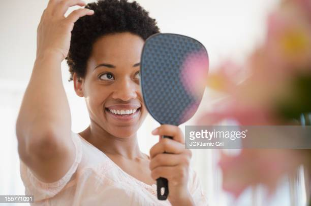 African American woman checking hair in mirror