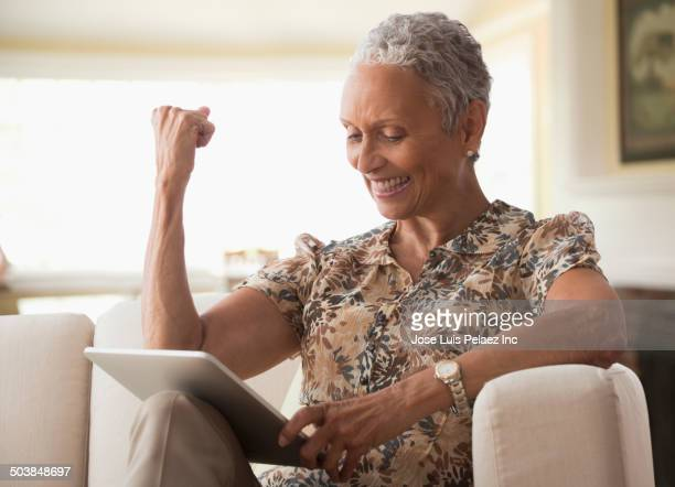 African American woman cheering at digital tablet