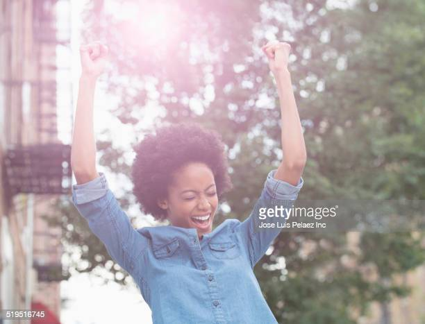 african american woman cheering in city - extatisch stockfoto's en -beelden