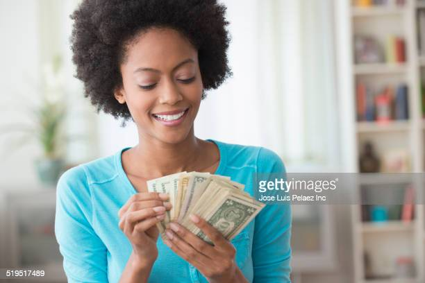 african american woman counting money in living room - currency stock pictures, royalty-free photos & images