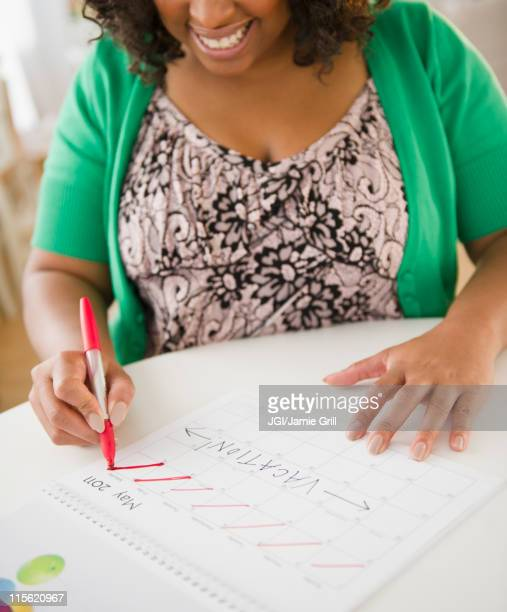 african american woman crossing off days on calendar - time management stock photos and pictures