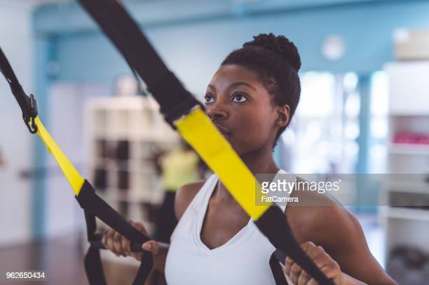 African American woman does a suspension workout at a modern gym