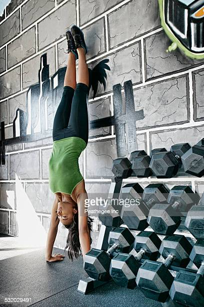 African American woman doing handstand in gym