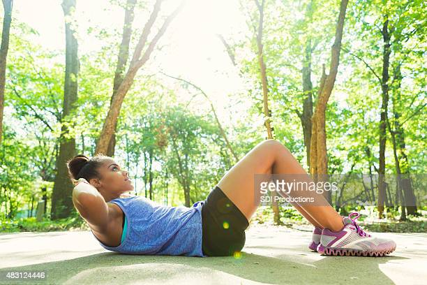 african american woman doing sit-ups during outdoor workout - sit ups stock photos and pictures