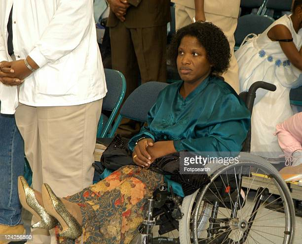 african american woman dressed in a skirt and high heels, sitting in her wheelchair waiting for an event to begin in an auditorium. - bound in high heels stock photos and pictures