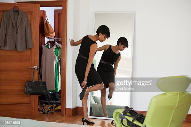 African American woman dressing in bedroom