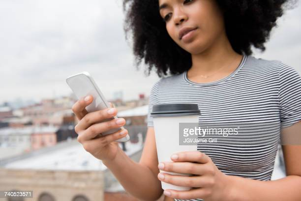 African American woman drinking coffee and texting on cell phone