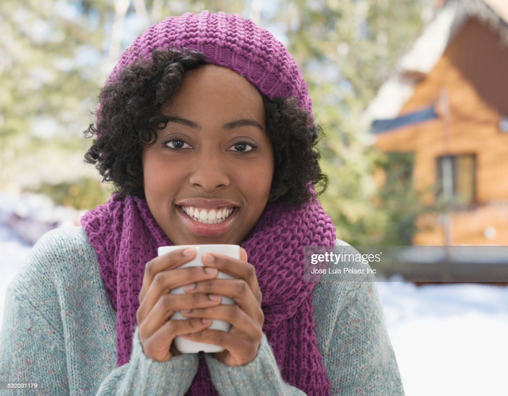 African American woman drinking cup of coffee in winter : Stock Photo