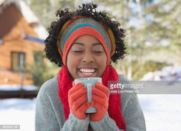 african american woman drinking cup of coffee in winter - warme dranken stockfoto's en -beelden