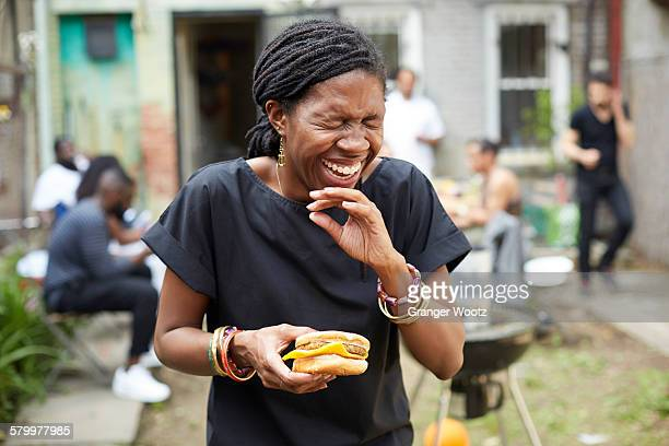 african american woman eating at backyard barbecue - femmes d'âge moyen photos et images de collection