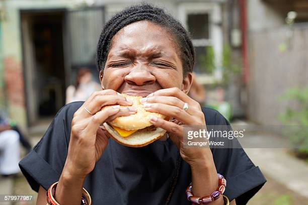 African American woman eating at backyard barbecue