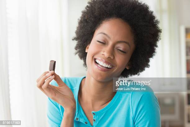 African American woman eating square of chocolate