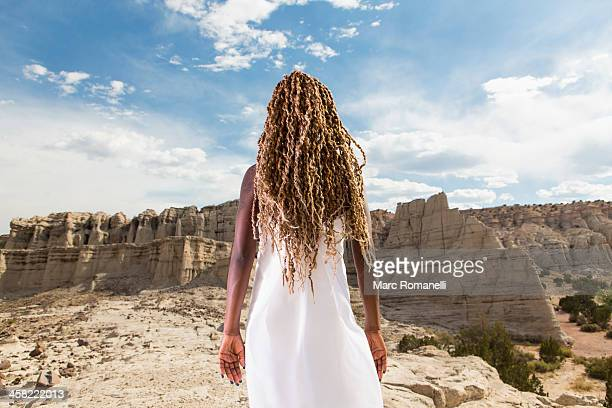 African American woman examining rock formations, Santa Fe, New Mexico, United States