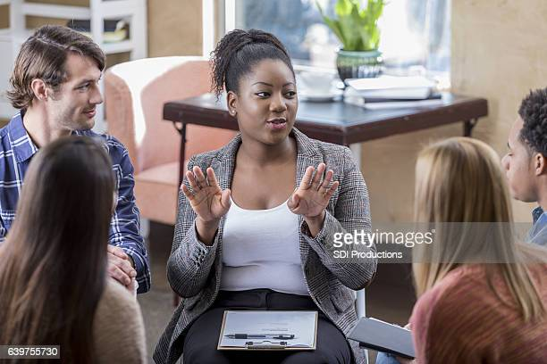 African American woman gestures during meeting with colleagues