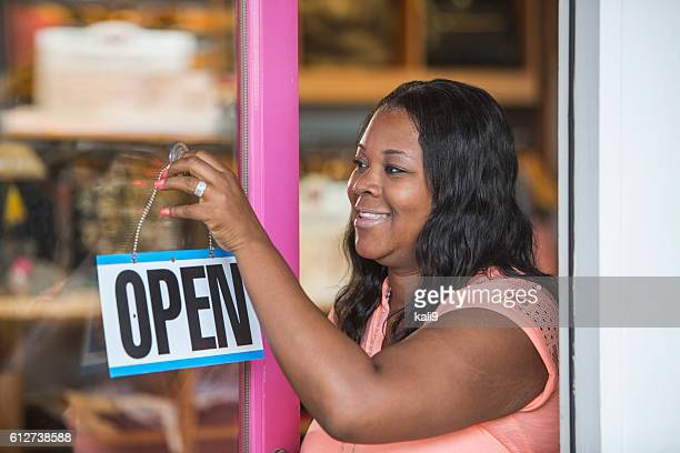 african american woman hanging open sign on store door - opening ceremony stock pictures, royalty-free photos & images