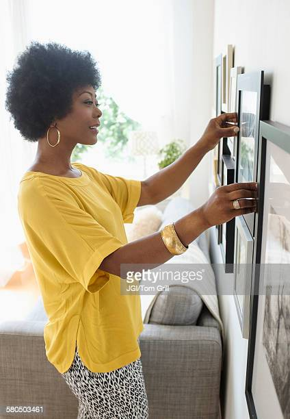 african american woman hanging pictures on living room wall - hanging stock pictures, royalty-free photos & images