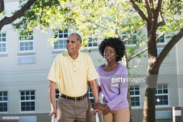 African American woman helping her father with walker