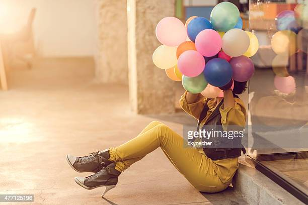 African American woman hiding behind bunch of colorful balloons.