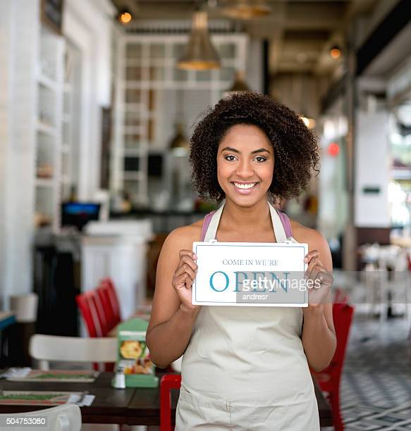 African American woman holding an open sign at a restaurant