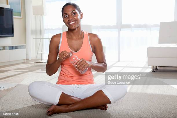 african american woman holding bottle of water - sleeveless top stock pictures, royalty-free photos & images