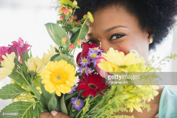 African American woman holding bouquet of flowers