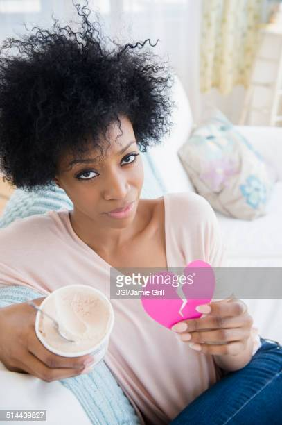 African American woman holding broken heart and ice cream