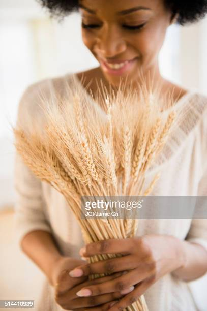 African American woman holding bunch of wheat