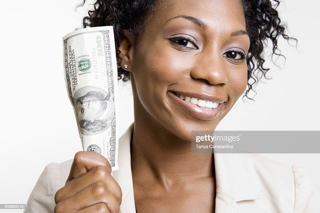 African American woman holding hundred dollar bill : Stock Photo