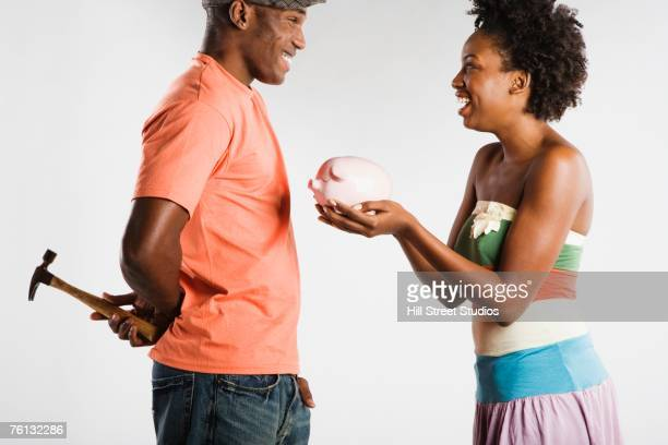 African American woman holding piggybank and man holding hammer
