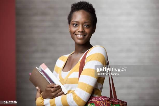 afro-americana mulher segurando livros escolares - estudante - fotografias e filmes do acervo