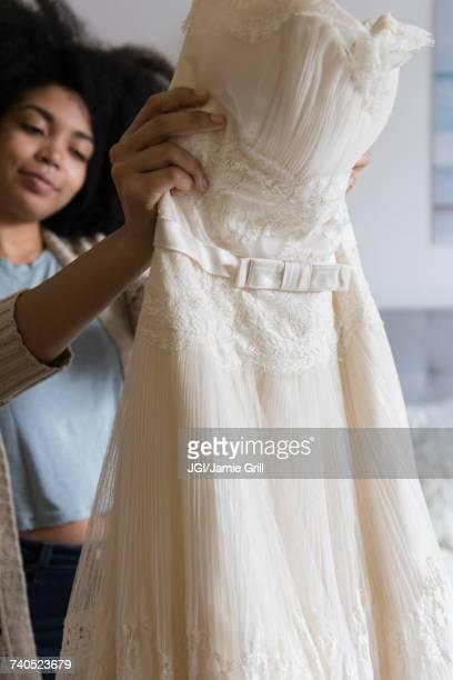 African American woman holding wedding dress