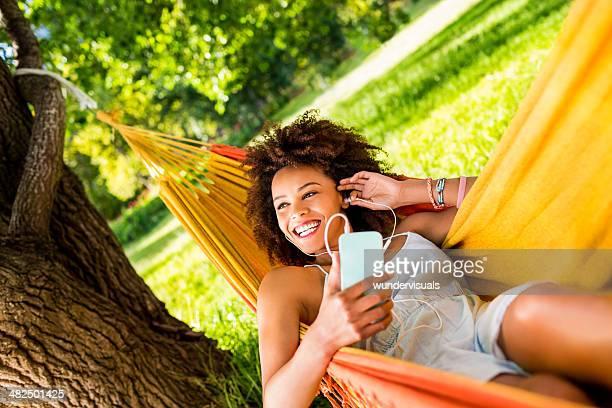 african american woman in a hammock enjoying music