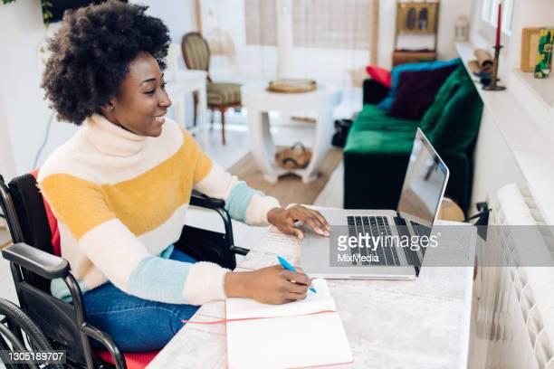 mulher afro-americana em uma cadeira de rodas trabalhando em casa - persons with disabilities - fotografias e filmes do acervo