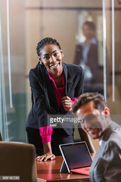 African American woman in boardroom giving presentation