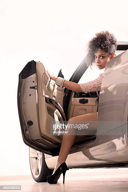 African American woman in convertible car looking at camera.