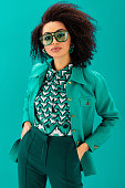 african american woman in jacket with hands in pockets looking at camera isolated on turquoise
