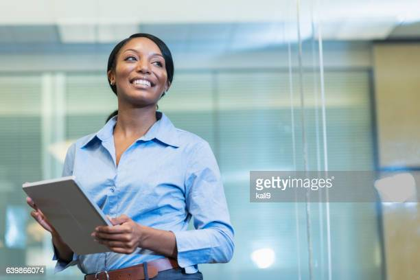 African American woman in office holding digital tablet