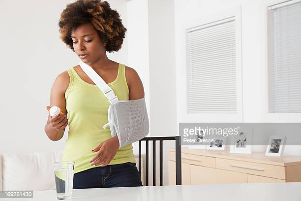 african american woman in sling taking medication - arm sling stock pictures, royalty-free photos & images