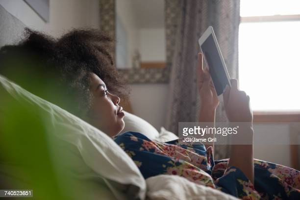 african american woman laying in bed reading digital tablet - using digital tablet stock photos and pictures