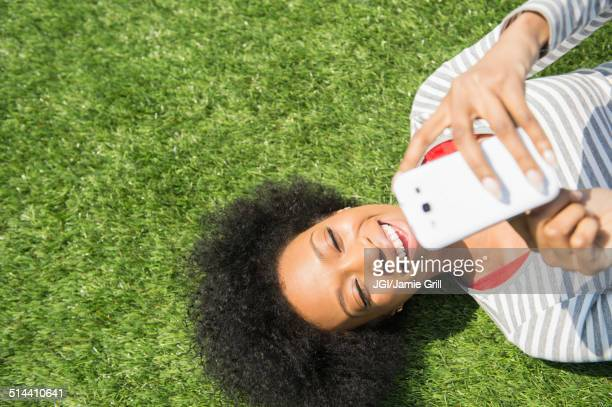 African American woman laying in grass using cell phone