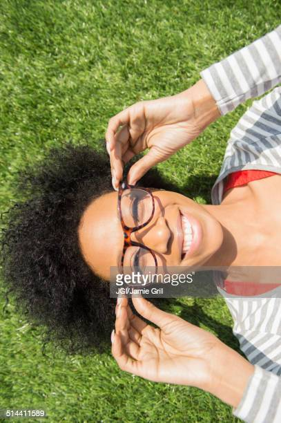 African American woman laying in grass wearing eyeglasses